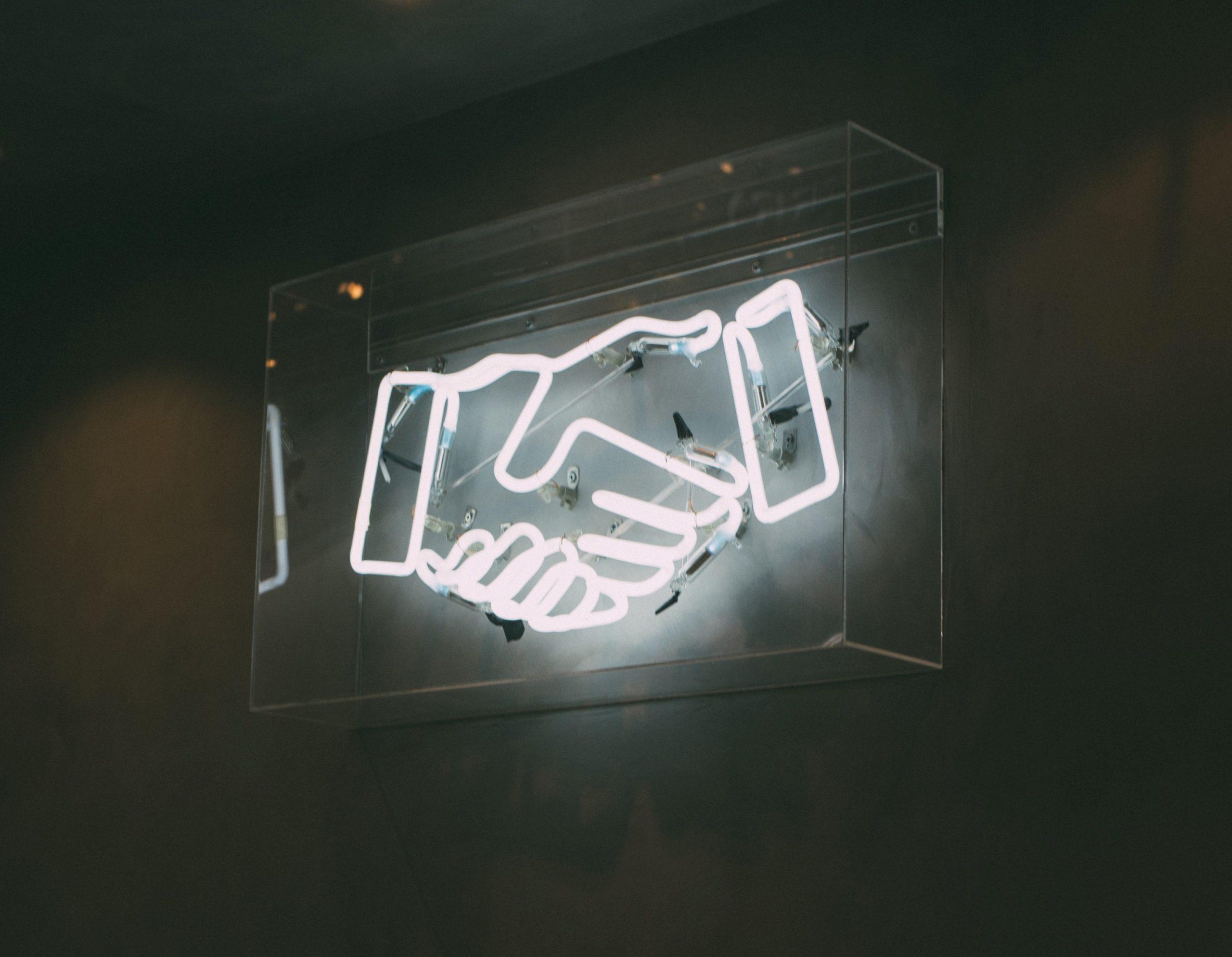 Stellenausschreibung bei Hennerkes Licht + Werbung. NEON Licht schüttelnde Hände.